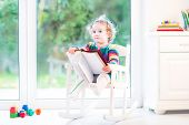 Cute Toddler Girl In A Colorful Knitted Dress Playing With A Book Sitting In A White Rocking Chair