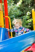 Happy Adorable Girl On Children's Slide On Playground