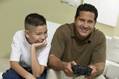 Son with father Playing Video Game on sofa in living room