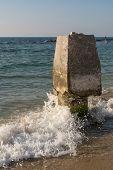 Wave crashing on a stone column