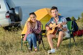 picture of serenade  - Cute man serenading his girlfriend on camping trip on a sunny day - JPG