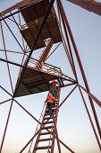 People Climbing Tower