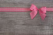 Top view of checked ribbon decoration on wooden background for christmas or for a voucher for birthday like a present