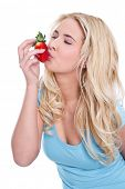 stock photo of strawberry blonde  - Caucasian blond woman kissing strawberry - JPG