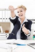 Caucasian blond businesswoman smiling and showing all right with her finger