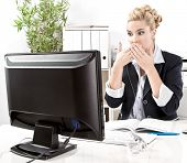 Blond woman sitting in office and getting shocked