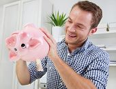 Smiling man trying to take money out from piggy bank