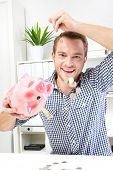 Happy young man taking out money from piggy bank