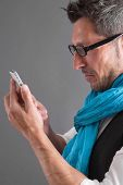 Man looking at his smart phone while text messaging.