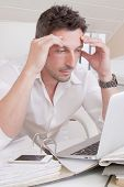 Man sitting frustrated at office looking at his liabilities.