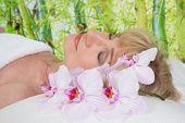 Senior woman lying on massage table in a beauty salon.