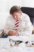 Businessman tied up with rope in the office - overworked senior businessman