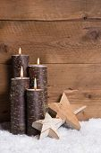Christmas decoration: burning candles,stars and snow on wooden background