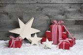 Red Christmas gifts with wooden starts on grey wooden background.