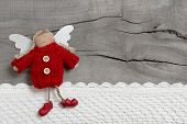 Red Christmas angel on grey wooden background