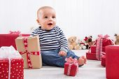 First Christmas: baby amongst red presents and is smiling
