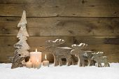 Wooden Christmas tree with elk or reindeer, four candles on wooden background for a greeting card