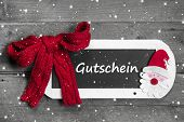 Red bow on chalk board with Voucher - coupon message on snowflake design grey wooden background - for christmas