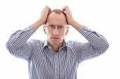 Frustrated man holding his head facing camera isolated on white background