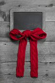 Menu board with a red ribbon for message with red knitted bow on grey wooden background