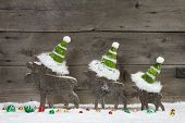 Funny christmas card with three elks wearing green santa hats for a greetings on a grey wooden background with snow for a greeting card