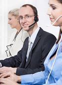 Telesales or helpdesk team - helpful man with headset smiling at camera - workers at call center
