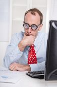 Overworked businessman with glasses staring into space at desk - stress and burnout