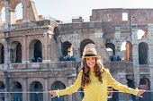 Portrait Of Young Woman In Front Of Colosseum In Rome, Italy