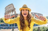 Young Woman Showing Thumbs Up In Front Of Colosseum In Rome, Ita