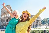 Happy Mother And Baby Girl Rejoicing In Front Of Colosseum In Rome, Italy