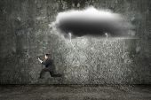 pic of rain cloud  - Running businessman holding tablet with dark clouds raining and lightning on concrete wall background - JPG