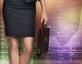 Business woman standing with a briefcase on background economic graphics