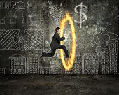 Businessman Holding Tablet Jumping Through Fire Hoop With Doodles Wall