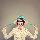stock photo of fool  - Studio Portrait of Smiling Hipster Girl in Funny Winter Hat Fooling Around and Tease - JPG