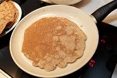 image of flaxseeds  - Pan with flaxseed meal pancake on a stove at home - JPG