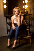 Blonde Woman Posing On Chair At Theater Dressing Room