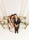 Young Man And Woman Sitting On Luxurious Sofa At Room