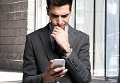 Puzzled man using his mobile phone