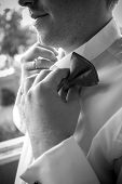Black And White Photo Of Elegant Man Adjusting Bow Tie