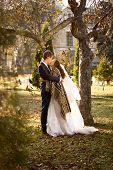 Groom Hugging Cute Bride Under Tree At Autumn Park