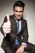 Happy young business man sitting while showing the thumbs up gesture, on grey studio background.