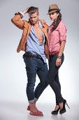 Full body picture of a fashion couple posing on studio background while looking down.