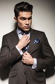 Portrait of a young business man fixing his tie while looking away from the camera. On grey studio background.