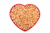Peas In A Dish In The Shape Of A Heart On A White Background.