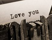 Typewriter with white paper page on wooden table. sample text Love you.