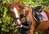 stock photo of feeding horse  - Outdoor portrait of beautiful woman feeding brown horse from hand - JPG