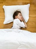 stock photo of floor covering  - Portrait of brunette little girl sleeping on floor covered with blanket - JPG