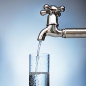 clean water is poured into a glass from the tap