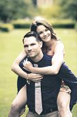 picture of fiance  - Instagram look of an image showing a handsome young man carrying his fiance on his back in a garden setting - JPG