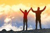 Happy winners reaching life goal - success people at summit. Business achievement concept. Two person couple together arms up in the air of happiness with accomplishment in the clouds at sunset.